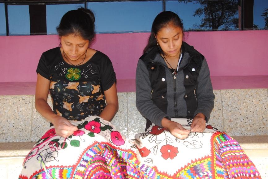 Maria Bautista Domingo och Patricia Perez Garcia broderar på en Nip i byn Yalambojoch i Guatemala.